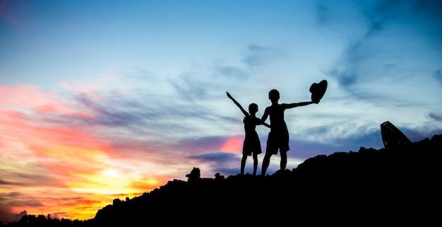 Jongens spelen bij zonsondergang.