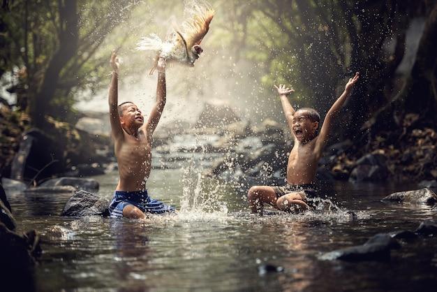 Jongens spelen met hun eend in de kreek