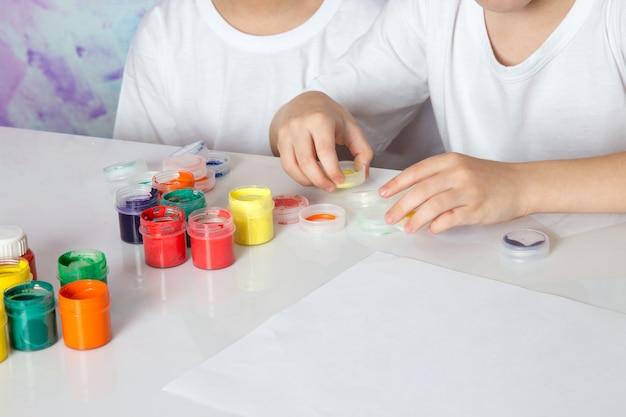 Jongens spelen met veelkleurige kleurrijke verf
