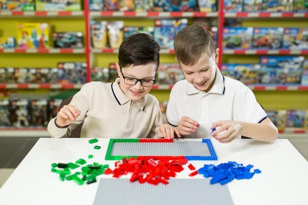 Jongens spelen samen met gekleurde plastic blokken in het speelcentrum, school.