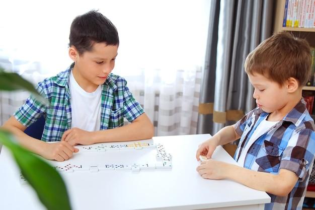 Jongens spelen thuis domino op tafel. het concept van vrije tijd in quarantaine-isolatie. oudere broer leert jongere broer domino spelen.