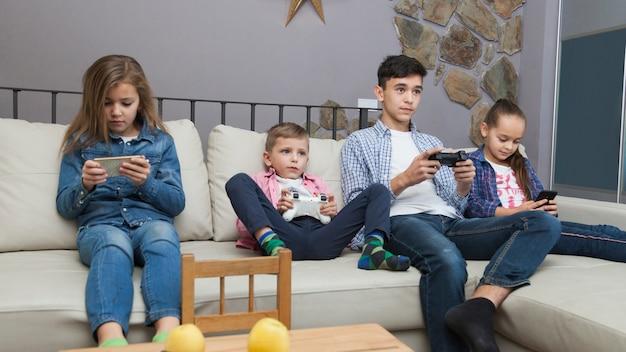 Jongens spelen videospellen en meisjes met behulp van smartphones