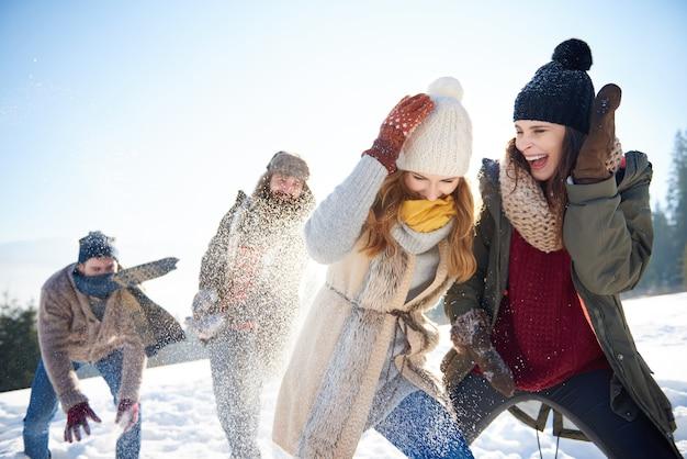 Jongens tegen meisjes in het sneeuwballengevecht