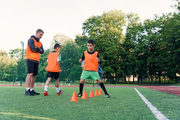 Jongens trainen tussen plastic kegels tijdens voetbaloefeningen in het stadion