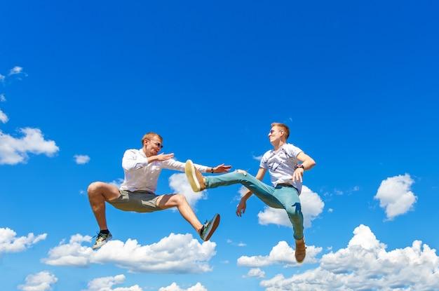 Jongens vechten in de lucht. jongens springen in de lucht en schoppen zijn vriend. jongens vechten in de lucht tegen de achtergrond van een blauwe lucht