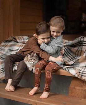 Jongens zitten op een houten trap knuffelen
