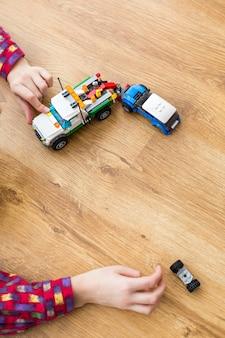Jongenshand met speelgoedauto's. kid spelen op houten vloer. deze moet gerepareerd worden. chauffeur heeft direct hulp nodig.