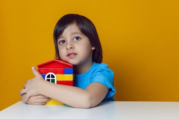 Jongenskind bouwer in een blauw t-shirt tegen een gele muur bouwt een huis uit kleurrijke plastic blokjes.
