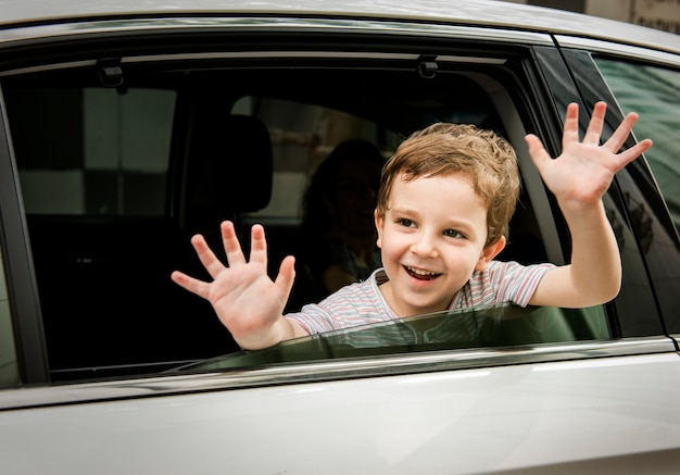 Jongenskind in auto vrolijke het glimlachen groet