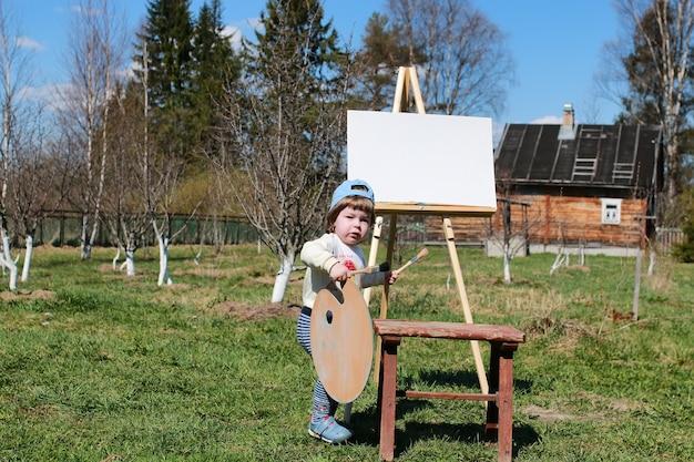 Jongenskind kunstenaar schildersezel borstel buiten