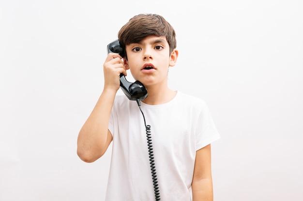 Jongenskind praten over vintage telefoon verrast