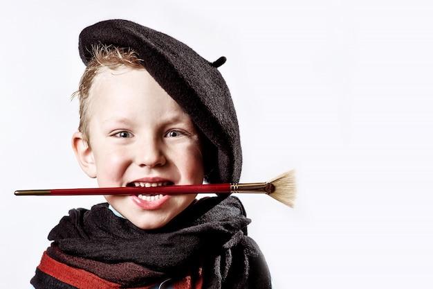 Jongenskunstenaar in zwarte baret, sjaal en met een borstel in zijn mond op een licht