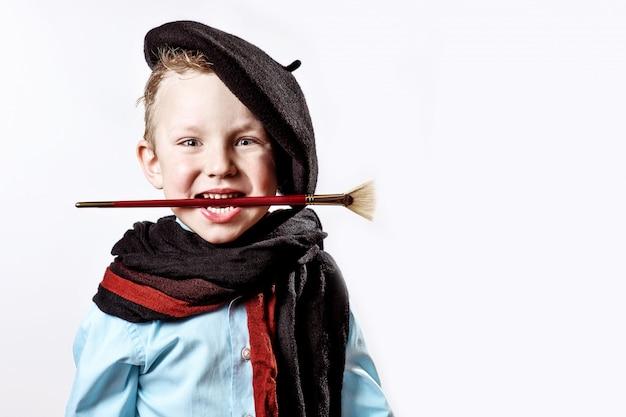 Jongenskunstenaar in zwarte baret, sjaal en met een borstel in zijn mond