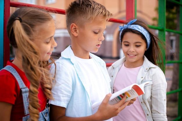 Jongenslezing uit een boek met twee meisjes