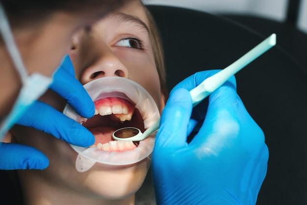 Jongenspatiënt die specialist in tandheelkundige kliniek bezoekt tandarts die jongenstanden onderzoekt
