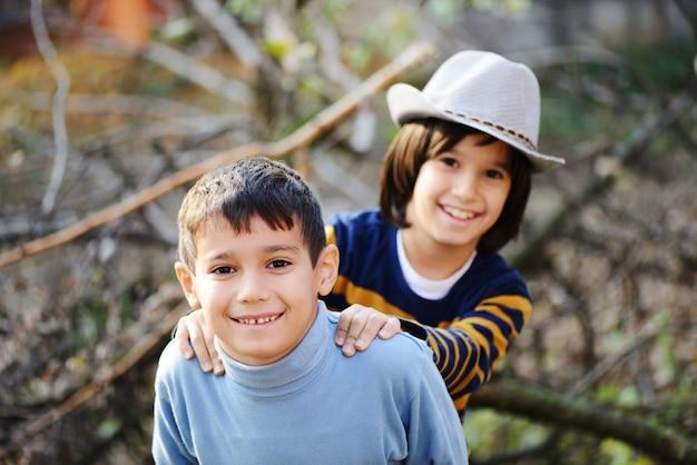 Jongensportret op boom openlucht in aard