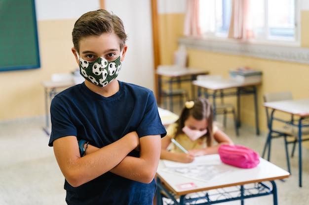 Jongensstudent die camera in het klaslokaal bekijkt die een masker draagt om zichzelf te beschermen tijdens de covid-pandemie