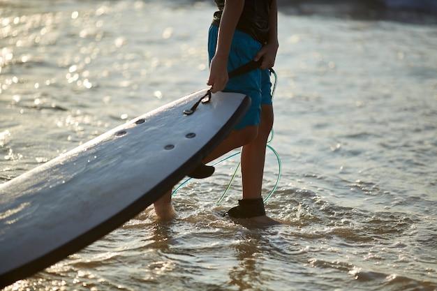 Jongenssurfer in oceaan met surfplank in werking wordt gesteld die. het waterplonsen en benen van het close-upbeeld, zonsonderganglicht