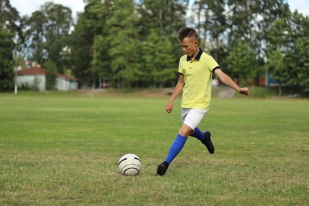 Jongensvoetballer in een geel t-shirt op een voetbalveld met een bal