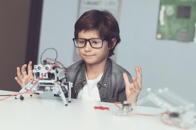 Jongenszitting bij bureau en het construeren van robot thuis