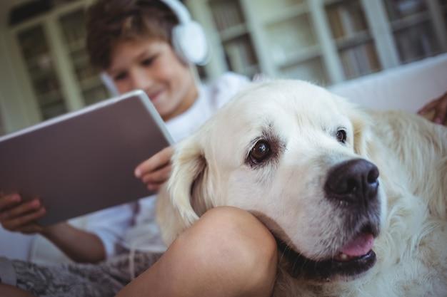 Jongenszitting op bank met huisdierenhond en het luisteren aan muziek op digitale tablet
