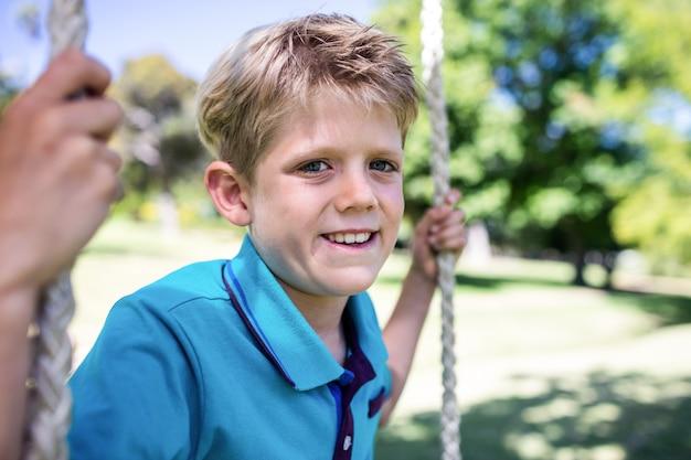 Jongenszitting op een schommeling in het park