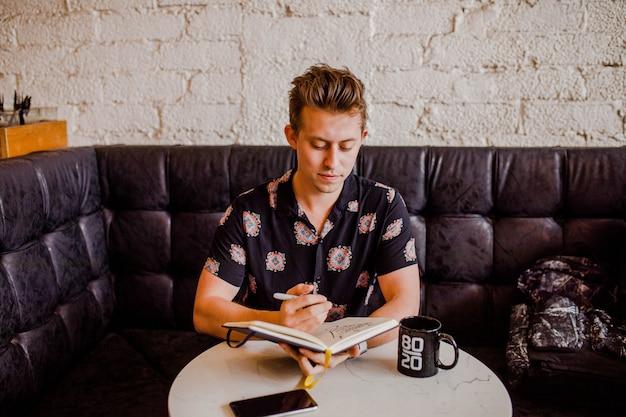 Jongenszitting op een zwarte bank en het nemen van nota's in een notitieboekje
