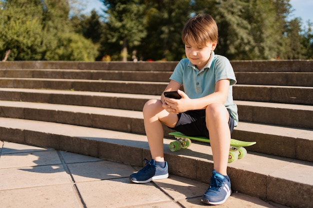 Jongenszitting op treden met smartphone in zijn hand en groene stuiverraad die grappige op video's letten