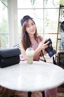 Jongere aziatische vrouw die dslr camera in hand met gelukgezicht houdt