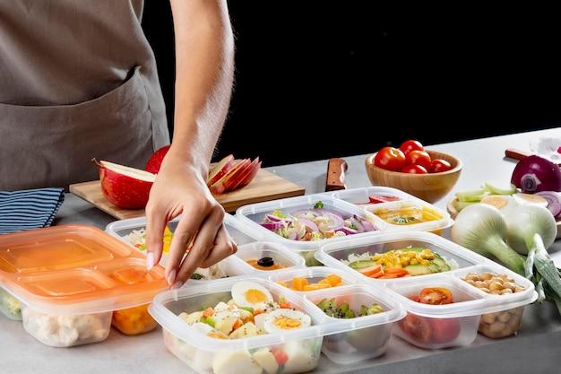 Jongere die batchcooking met gezond voedsel beoefent