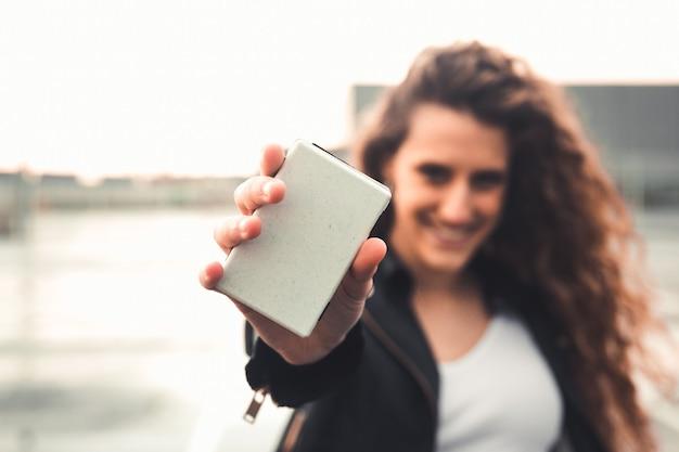 Jongere die een gefocuste portemonnee toont en de persoon die op straat niet gefocust is