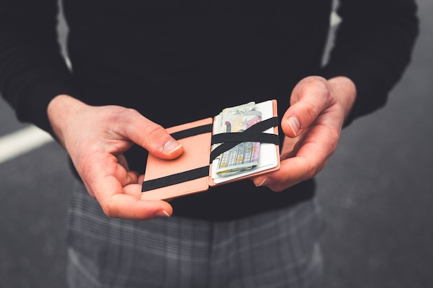 Jongere die een portemonnee controleert met euro's en kaarten