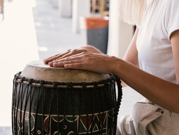 Jongere die latijns percussie-instrument speelt