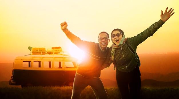 Jongere man en vrouwengelukemotie die naar bestemming reizen tegen mooie zonsonderganghemel