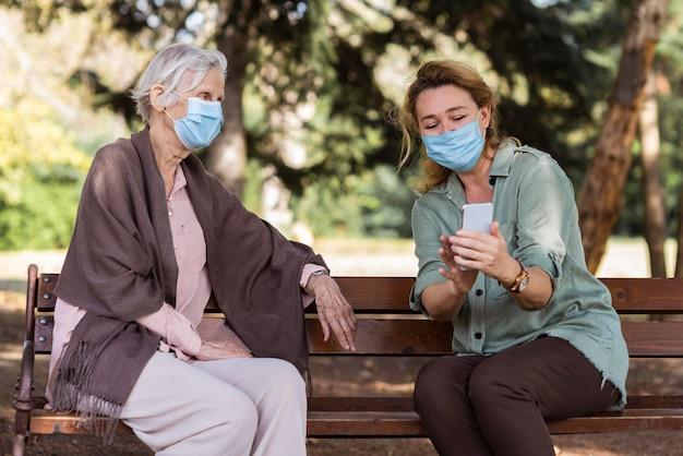 Jongere vrouw met medisch masker dat oudere vrouw op bank iets op smartphone toont