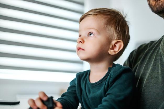 Jongere zit bij vader op schoot en kijkt naar iets met zijn mooie grote blauwe ogen.
