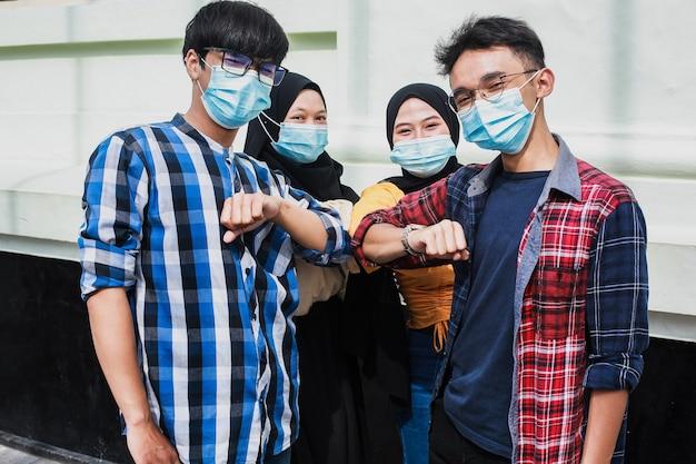 Jongeren begroeten elkaar met de elleboog of nieuwe handdruknormaliteit bij het coronavirus