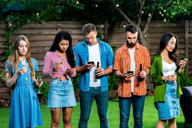 Jongeren buitenshuis met telefoons sms'en