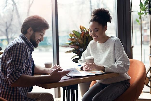 Jongeren coworking samen op creatieve kantoor zitten discu