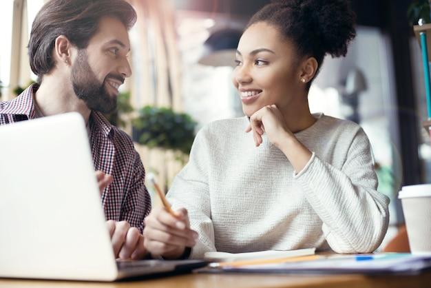 Jongeren coworking samen op creatieve kantoor zitten looki