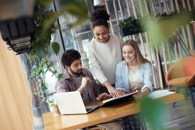 Jongeren coworking samen op creatieve kantoor zittende vrouw