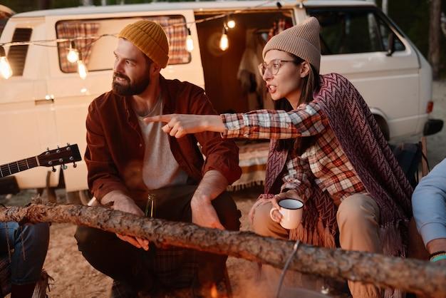 Jongeren die buiten op een picknick zitten en met elkaar praten bij het vuur