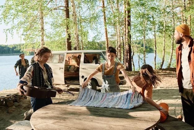 Jongeren die de tafel dekken, kamperen in het bos bij het meer