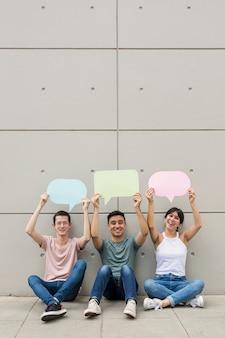 Jongeren die kleurrijke tekstballonnen houden