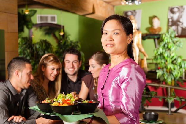 Jongeren die met serveerster in thais restaurant eten