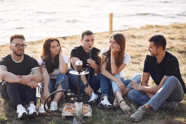 Jongeren die pizza eten en shisha roken bij het strand