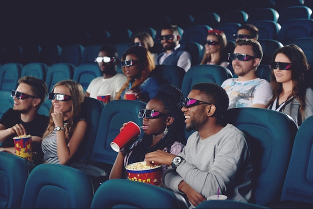 Jongeren die popcorn eten en cola drinken en vrije tijd in de bioscoop doorbrengen.