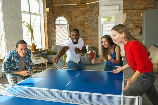 Jongeren die tafeltennis spelen op de werkplek, plezier hebben