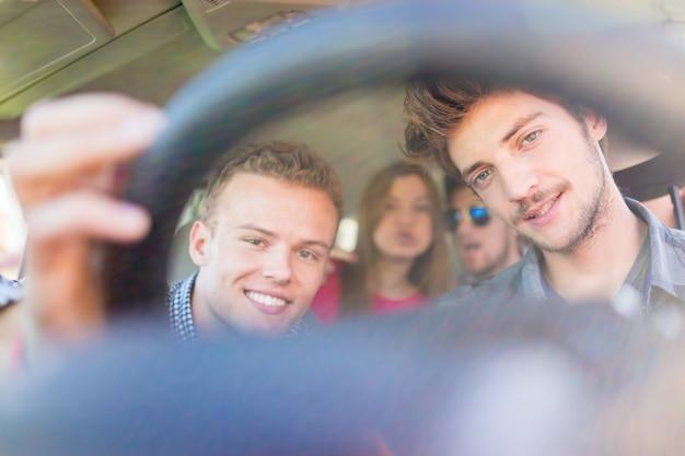 Jongeren die vakantie hebben die van plezier rijdende auto genieten
