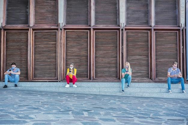 Jongeren die veiligheidsmaskers dragen met slimme mobiele telefoons terwijl ze afstand houden